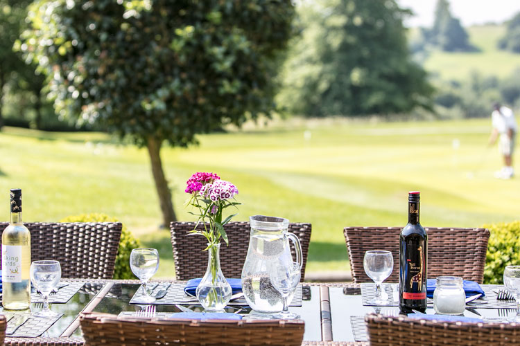 A set dining table on a patio in summer with a golfer on a green behind.