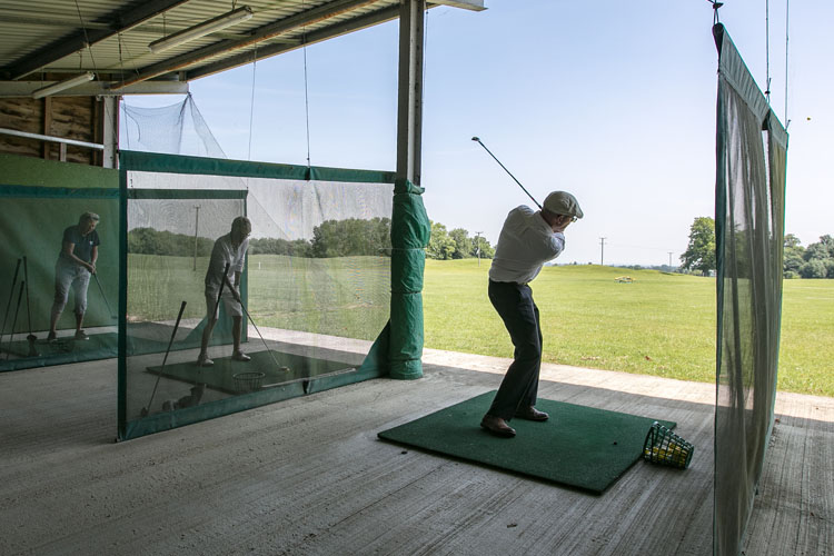 Golfers on a driving range.